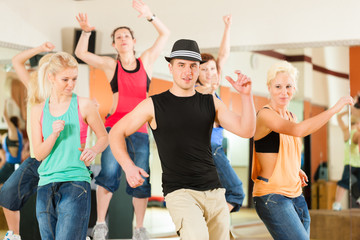 Zumba or Jazzdance - young people dancing in studio