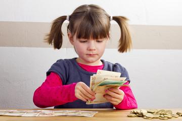 Mädchen zählt Geldscheine