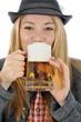 Junge Frau in bayrischer Kleidung trinkt Bier