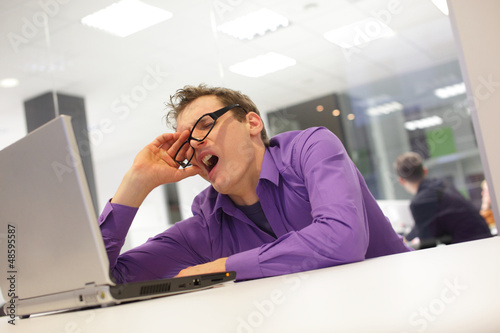 bored yawning businessman with laptop in the office