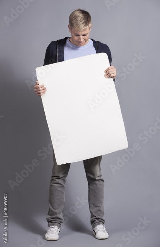 Pleased man holding white blank signboard.