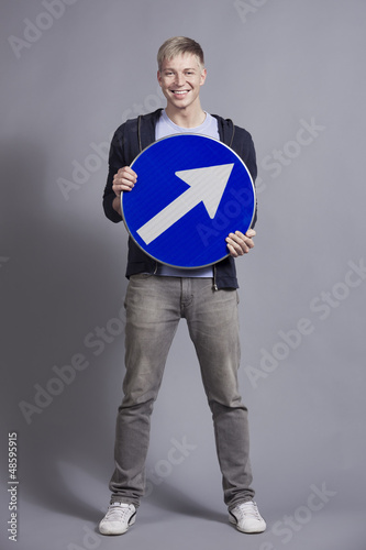 Joyful man holding round blue sign with arrow.