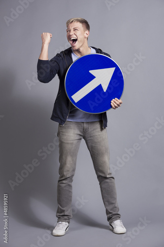 Overjoyed man holding round blue sign with arrow.