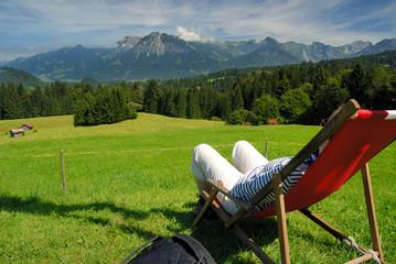 Wanderer im Liegestuhl geniesst das Alpenpanorama