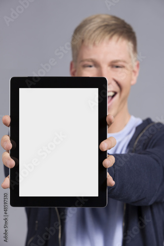 Joyful man presenting tablet.