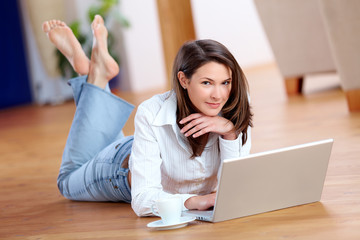 Beautiful young woman with laptop on the floor