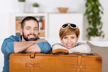 junges paar stützt sich auf reisekoffer