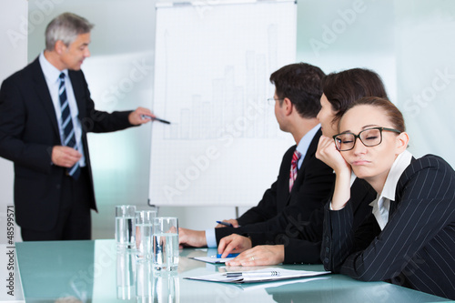 Bored businesswoman sleeping in a meeting