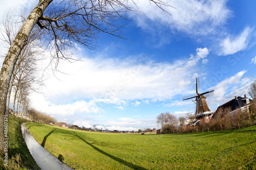 Dutch windmill on green pasture