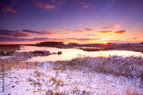 dramatic sunrise over frozen lake