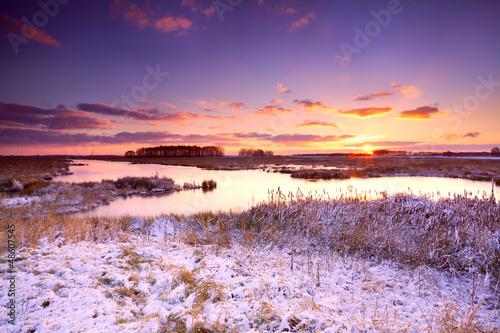 dramatic sunrise over frozen lake