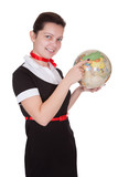 Pretty flight attendant holding a globe