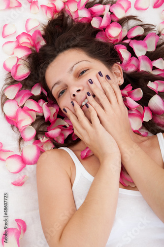 Rose petals surround a woman laying on a bed