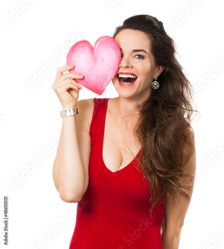 Laughing woman holding a love heart over her eye.