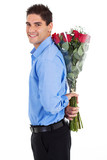 young man hiding bunch of red roses behind his back