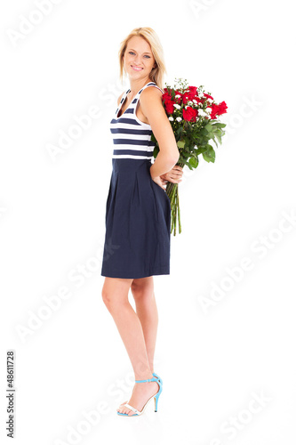 pretty young woman hiding roses behind her back