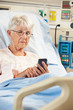 Senior Female Patient In Hospital Bed Using Mobile Phone