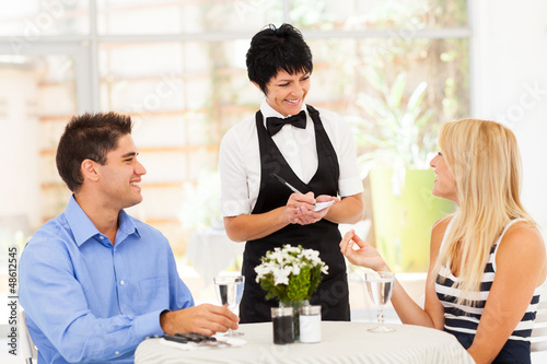 friendly middle aged waitress taking order from customer