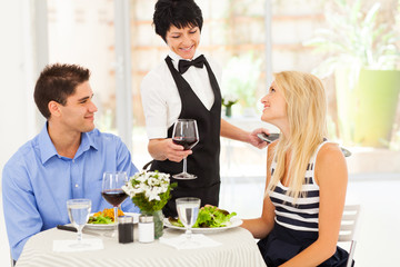 waitress serving wine to diners in modern restaurant