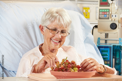 Senior Female Patient Eating Grapes In Hospital Bed