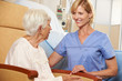 Nurse Taking To Senior Female Patient Seated In Chair