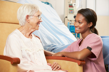 Nurse Talking To Senior Female Patient Seated In Chair
