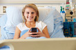 Teenage Female Patient Using Mobile Phone In Hospital Bed