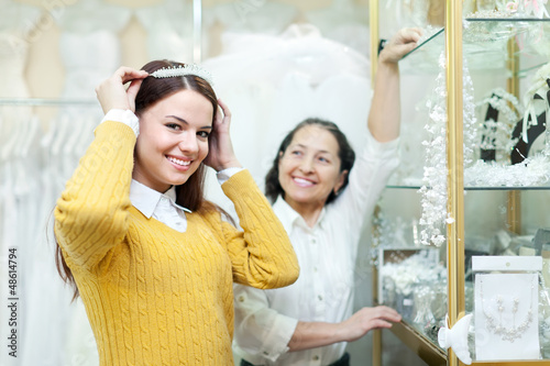 woman helps the bride in choosing bridal diadem