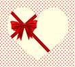Red ribbon cover on heart shape over polka dot