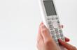 電話機とボタンを押す指と手