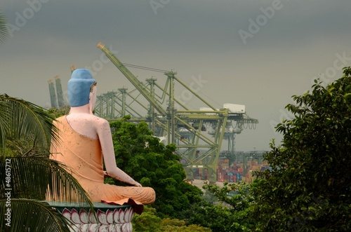 Seated meditating Buddha in views busy container seaport