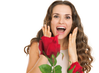 Surprised young woman receiving red roses