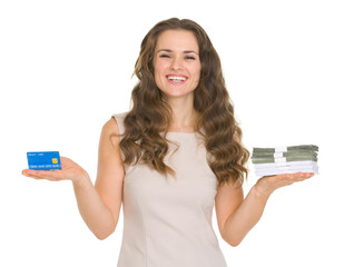 Happy young woman scaling credit card and money packs on hands