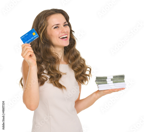 Happy young woman holding credit card and money packs