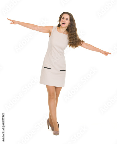 Full length portrait of happy young woman balancing