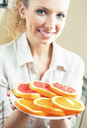 Woman with plate of oranges and grapefruit