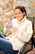Smiling woman drinking tea patio sweater relaxing