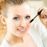 Cheerful woman applying mascara with lash brush poster