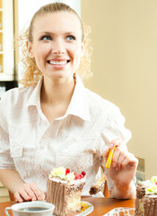 Cheerful blond young woman eating torte