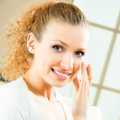 Happy smiling woman applying creme, indoor