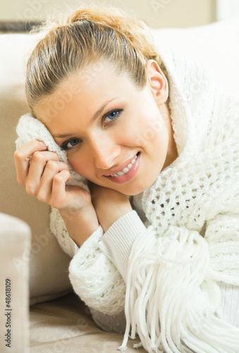 Cheerful blond young woman in scarf indoors