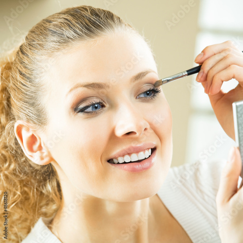 Cheerful woman with mirror and makeup brush