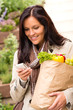 Smiling woman shopping vegetables mobile phone sms