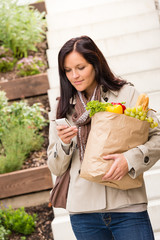 Young woman holding groceries vegetables shopping phone