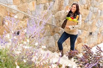 Smiling woman climbing stairs talking phone shopping