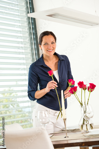 Happy woman putting bouquet dinner table