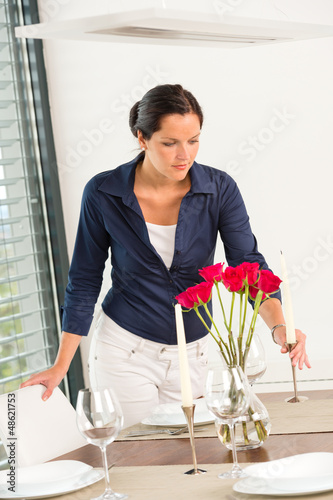 Young woman placing candle table roses romantic