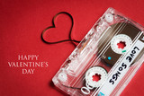 audio cassette with tape in shape of heart on red background