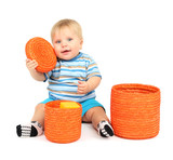 Little boy playing with color wicker boxes, isolated on white