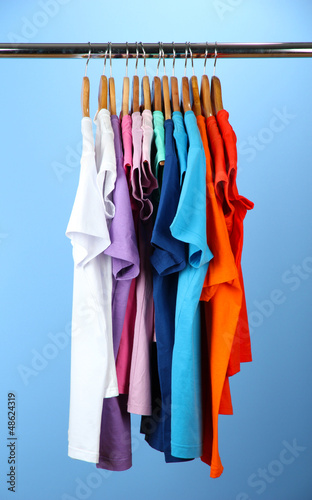 Variety of casual shirts on wooden hangers,on blue background
